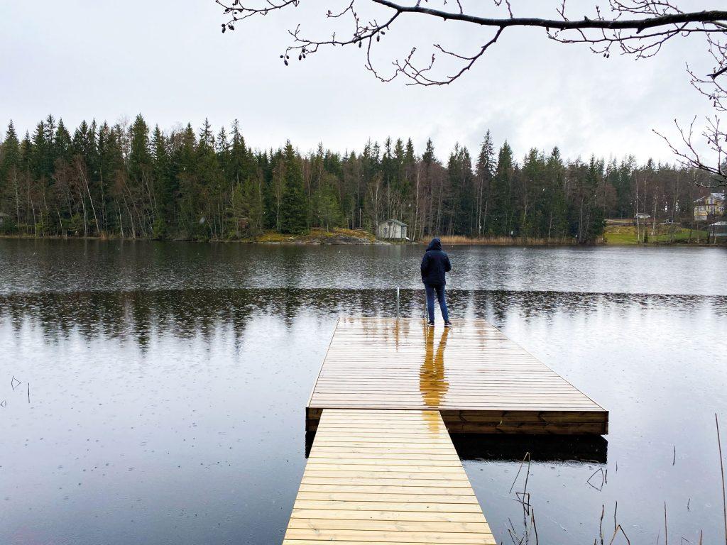 Laituri järven rannassa. Sataa vettä, nainen seisoo laiturilla.